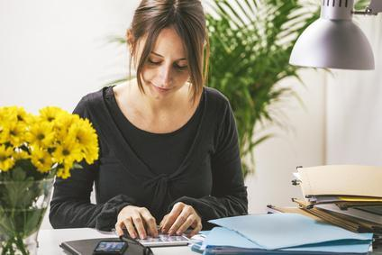 Young casual woman using digital tablet in office.